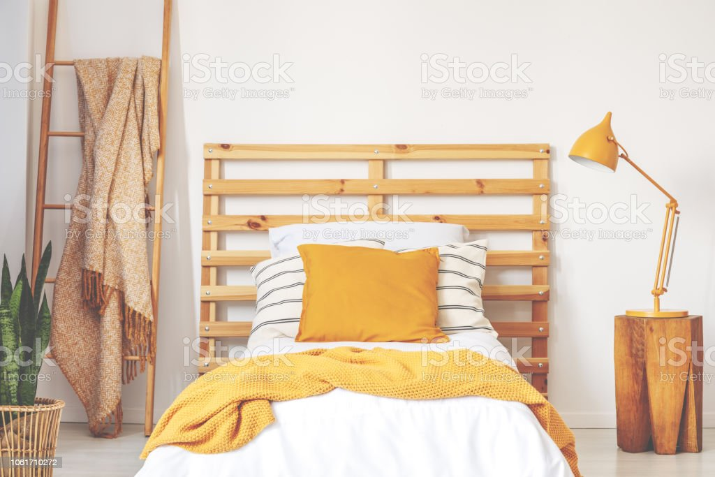 Yellow cushions on wooden bed with blanket in bedroom interior with lamp, plant and ladder. Real photo stock photo