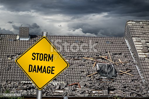 istock yellow damage warning sign in front of storm damaged roof of house 1062918764