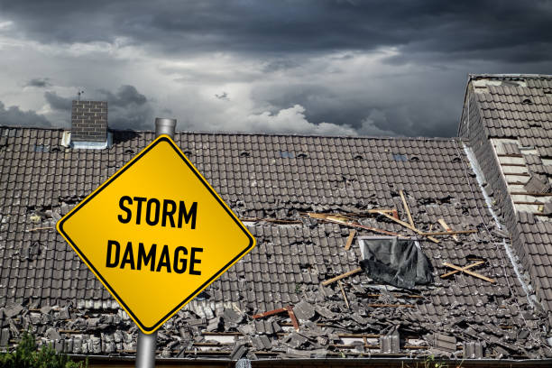 yellow damage warning sign in front of storm damaged roof of house stock photo
