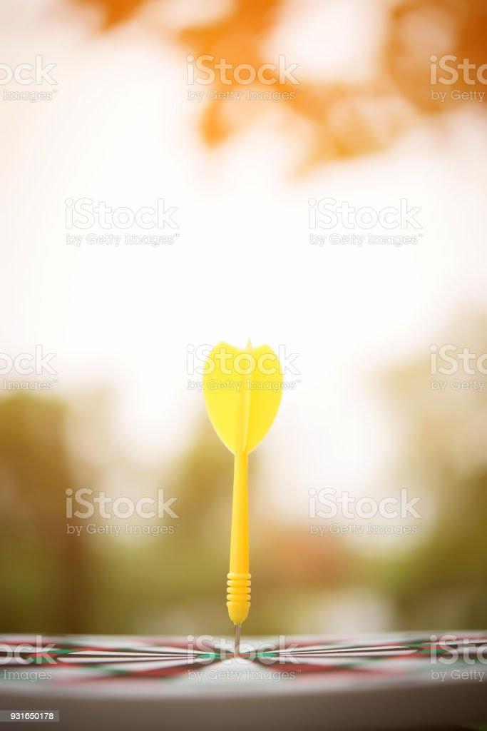 Yellow dart arrow hitting in the center of dartboard. stock photo