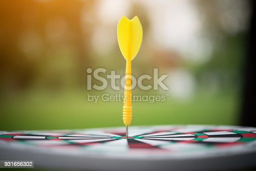 istock Yellow dart arrow hitting in the center of dartboard. 931656302
