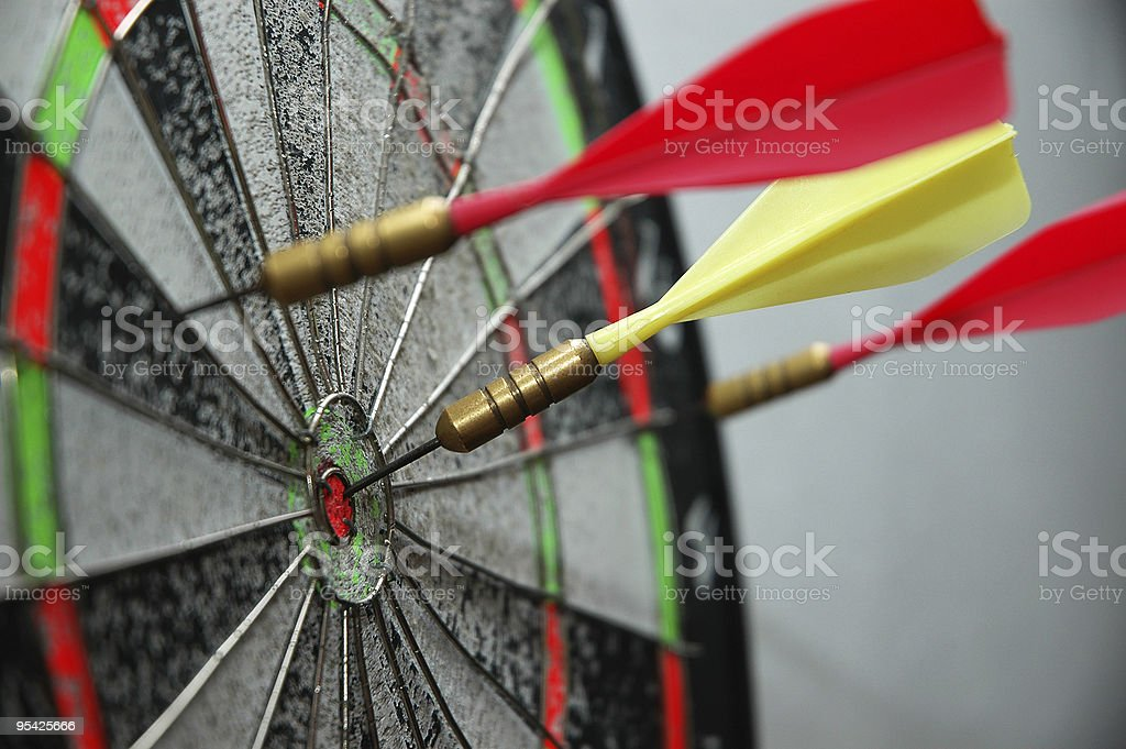 Yellow dart on a bullseye with red darts around it stock photo