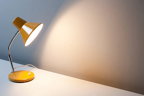 gelbe schreibtisch-lampe auf tisch - bürolampe stock-fotos und bilder
