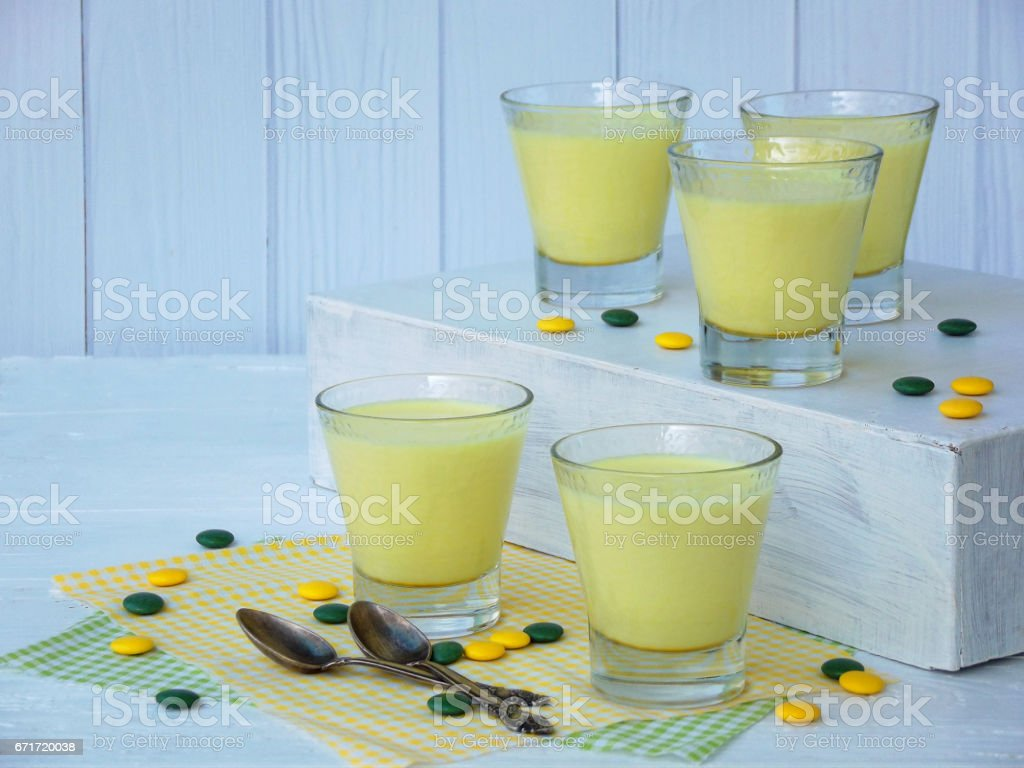 Yellow dessert Junket from milk and rennet extract with turmeric in glasses on light background. Jelly-like pudding made from sweet cottage cheese. Healthy food. Space for text stock photo