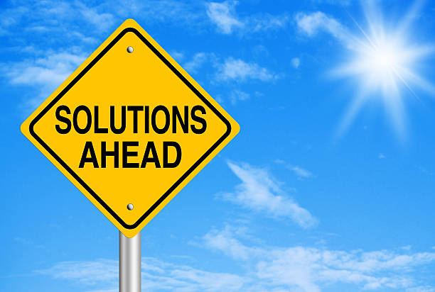 Yellow diamond sign reading 'solutions ahead' with behind  stock photo