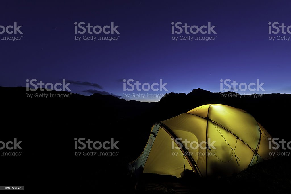 Yellow dome tent illuminated starry mountain night royalty-free stock photo