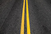 Yellow double dividing lines, highway road marking on dark asphalt