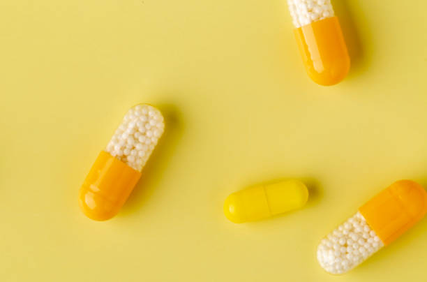 Yellow drug soluble capsules with microgranules inside. stock photo