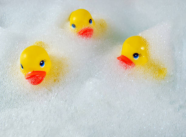 yellow ducks in bubble bath yellow toy rubber ducks floating in bubble bath suds bubble bath stock pictures, royalty-free photos & images