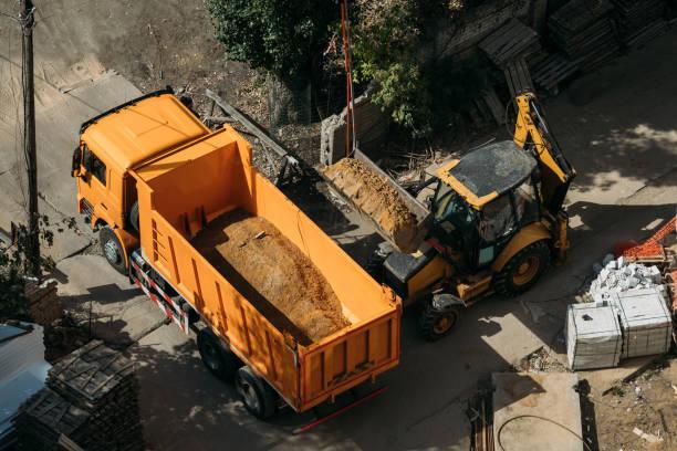 gelber Muldenkipper und gelber Traktor lädt Sand-Top-Ansicht auf einer Baustelle – Foto