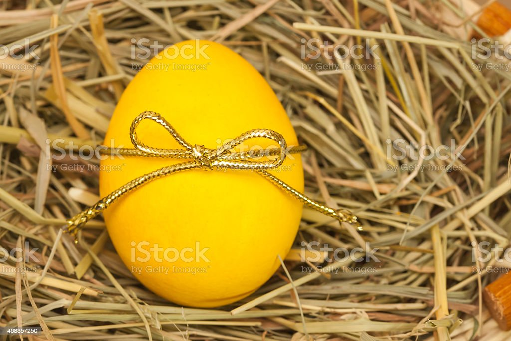 yellow egg with bowknot on hay background royalty-free stock photo