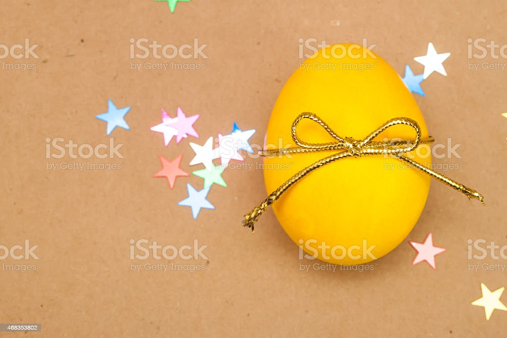 yellow egg with bowknot on kraft background royalty-free stock photo
