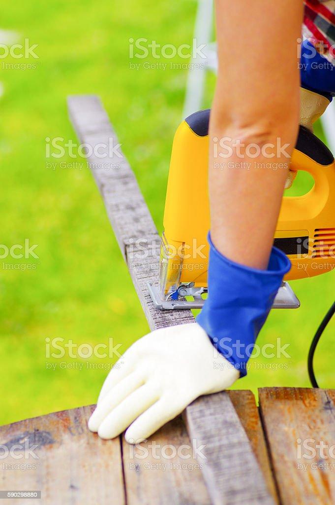 yellow electric jigsaw cutting a piece of wood Стоковые фото Стоковая фотография