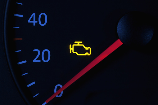 yellow engine check engine icon on car dashboard, black background