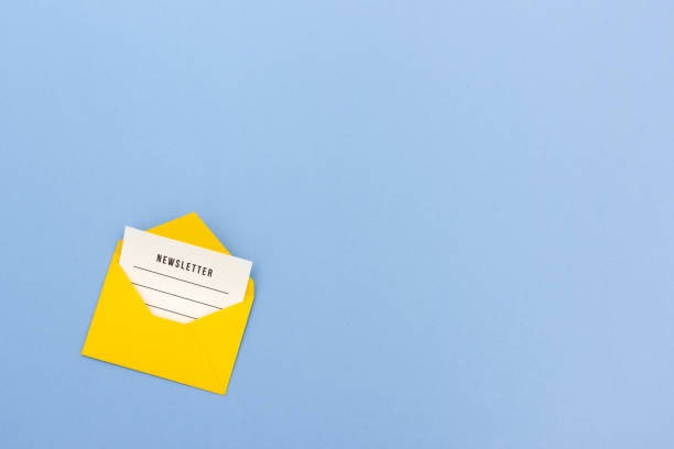 Yellow envelope with newsletter on blue background Minimalist arrangement of bright yellow envelope with blank of newsletter inside on blue backdrop newsletter stock pictures, royalty-free photos & images