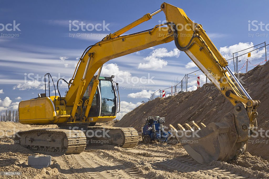 Yellow Excavator against blue sky stock photo
