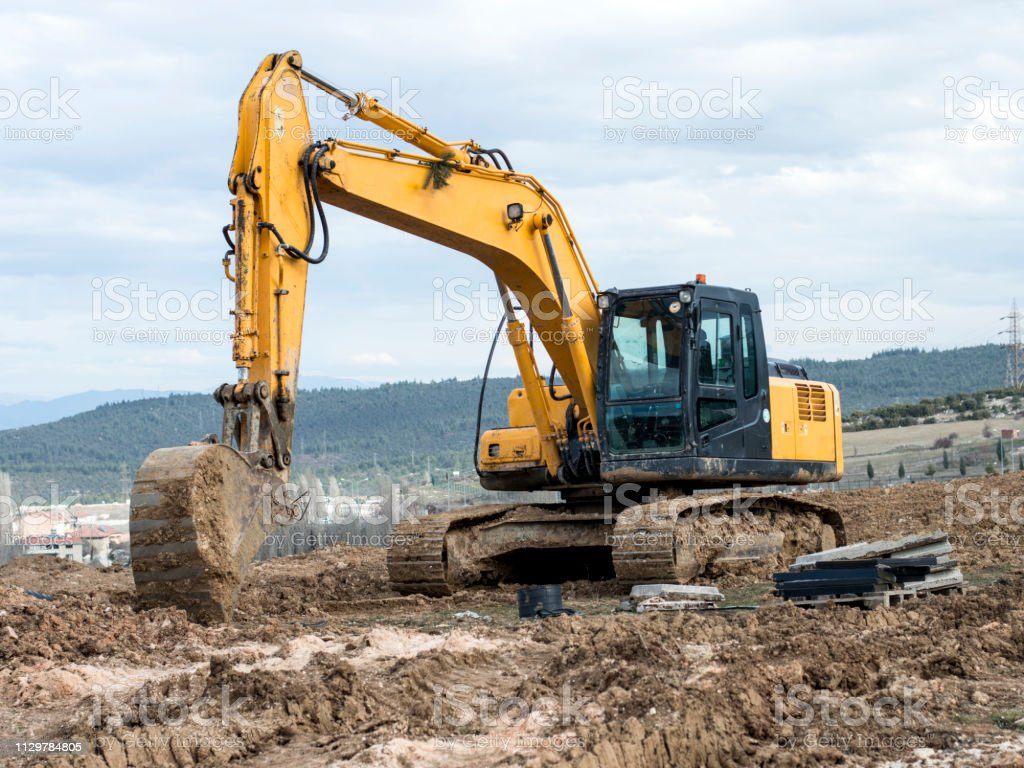 Yellow Excavator At Construction Site Into Mud With Sky
