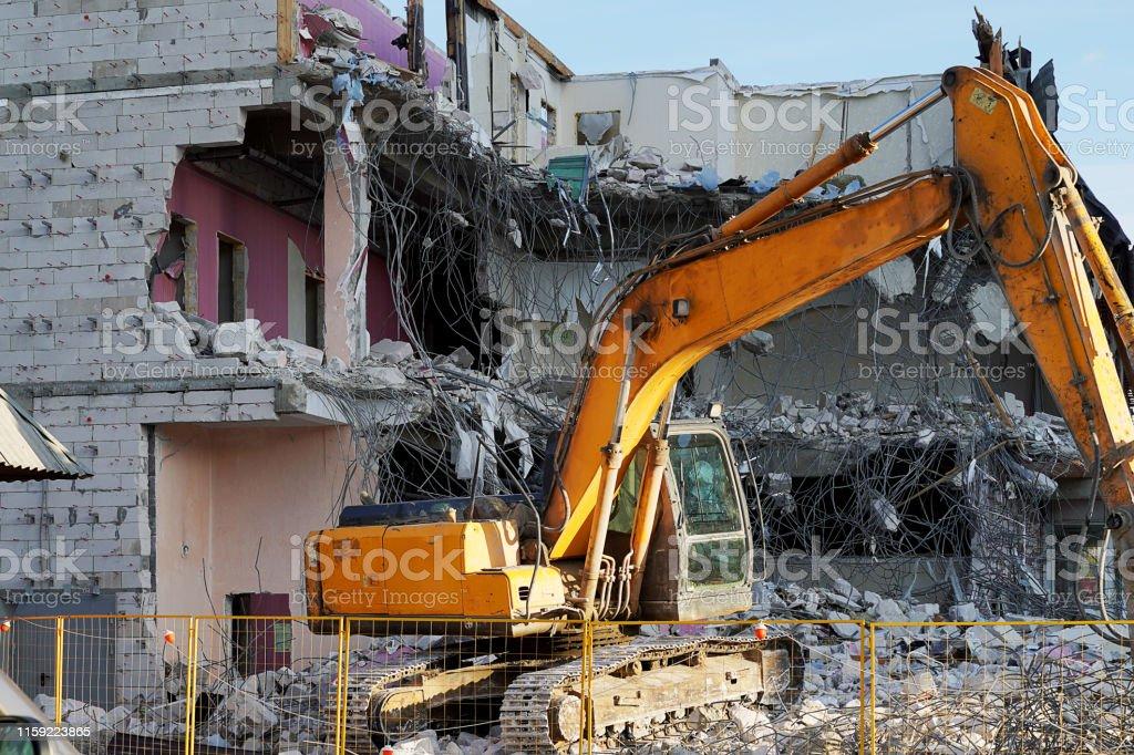 Yellow Excavator Demolishing A Multistorey Building