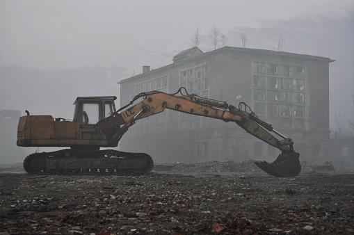 Yellow excavator digger demolishing old building