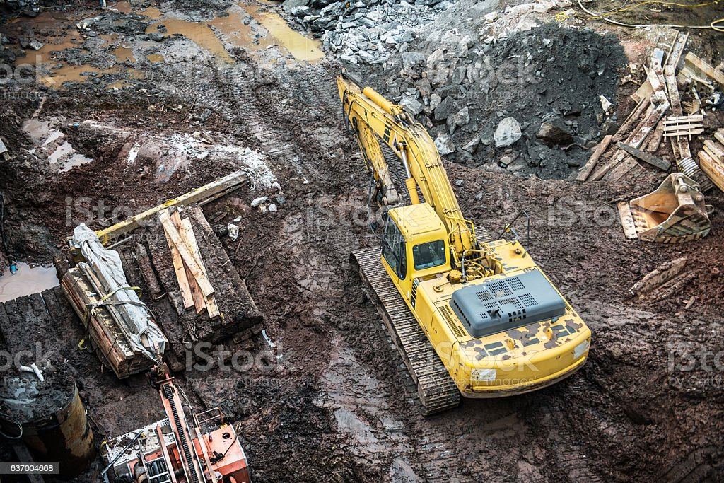 Yellow excavator digging on construction site. stock photo