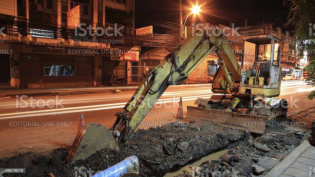 Yellow Excavator Digging Street At Night In Korat Downtown Stock