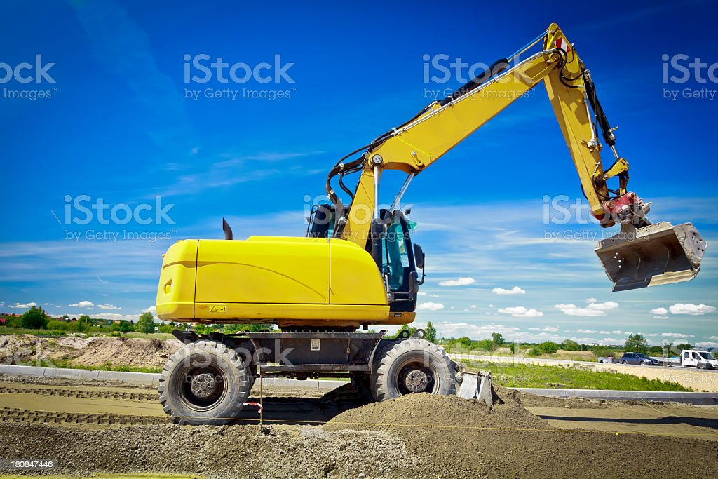 Yellow excavator in a new road construction royalty-free stock photo