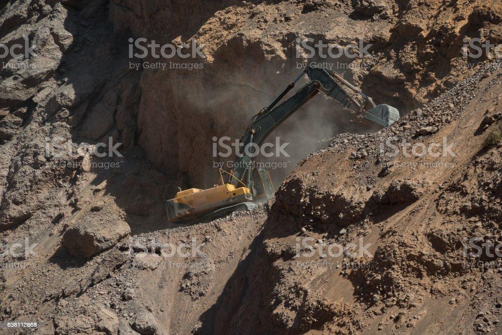 Yellow excavator in mountains stock photo
