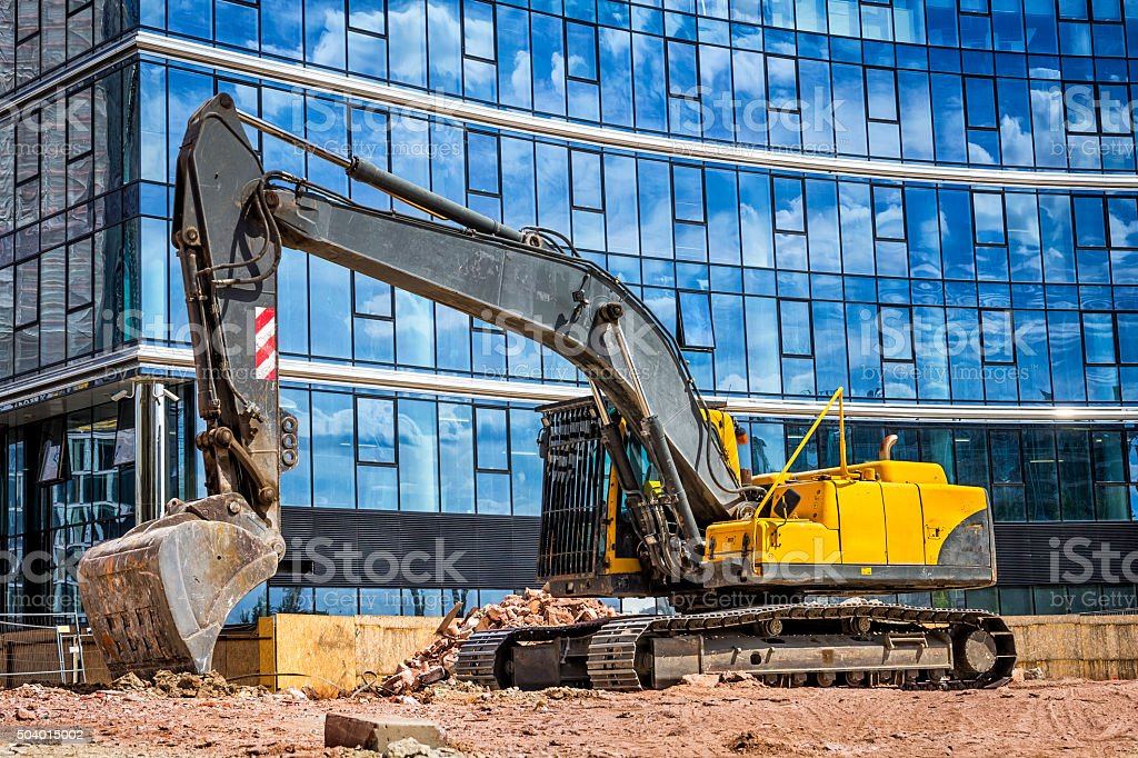 Yellow excavator on construction site stock photo