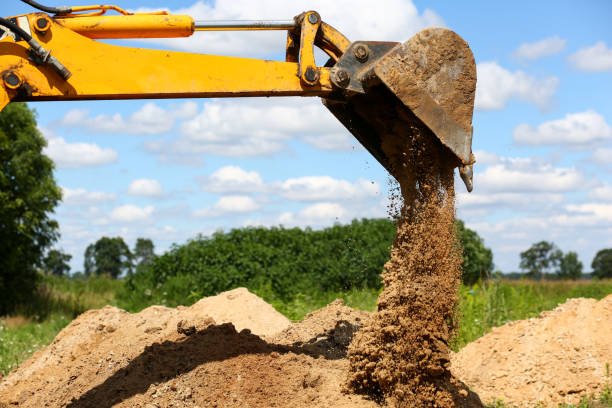 Yellow excavator shovel digging pit in ground stock photo