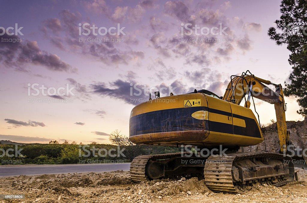 Amarelo excavator parada durante o pôr-do-sol - foto de acervo