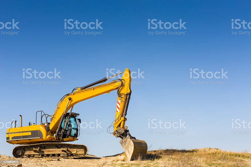 yellow excavator under a clear blue sky stock photo