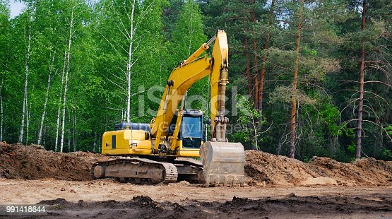 yellow excavator with a crawler on a caterpillar track, works on the construction of a highway