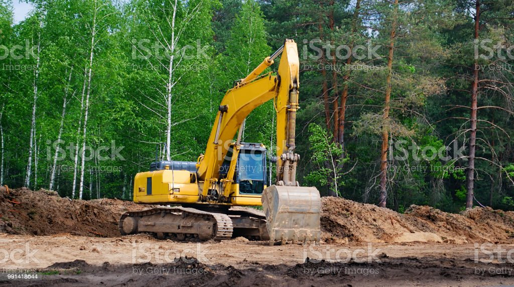 yellow excavator with a crawler on a caterpillar track, works on the construction of a highway stock photo