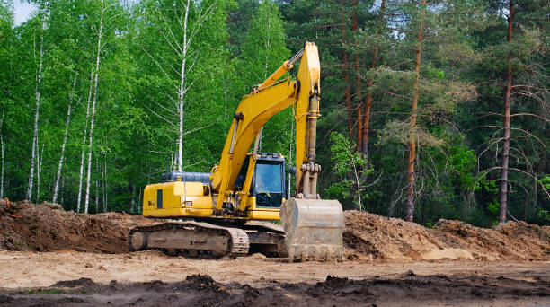 yellow excavator with a crawler on a caterpillar track, works on the construction of a highway yellow excavator with a crawler on a caterpillar track, works on the construction of a highway archaeology stock pictures, royalty-free photos & images