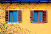 Yellow facade of a house with windows with brown shutters. Croatia