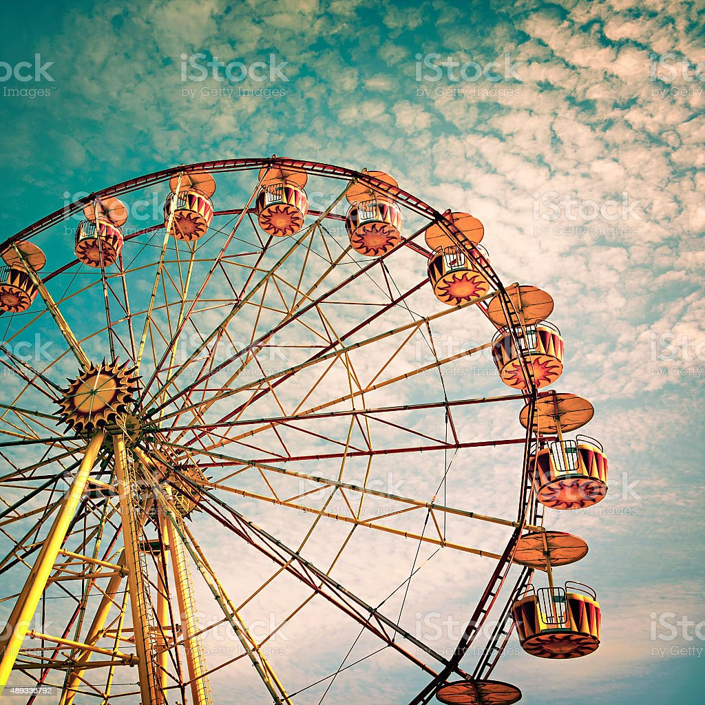 yellow ferris wheel against a blue sky in vintage style stock photo