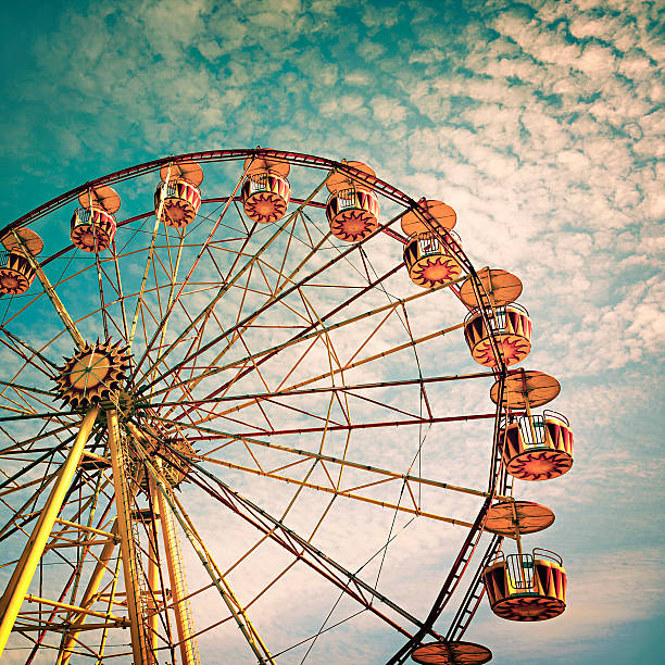 yellow ferris wheel against a blue sky in vintage style yellow ferris wheel against a blue sky in vintage style  ferris wheel stock pictures, royalty-free photos & images