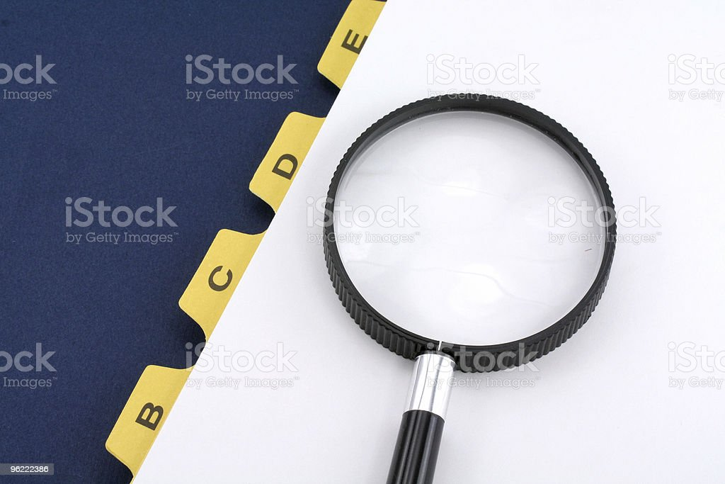yellow file divider and magnifier stock photo