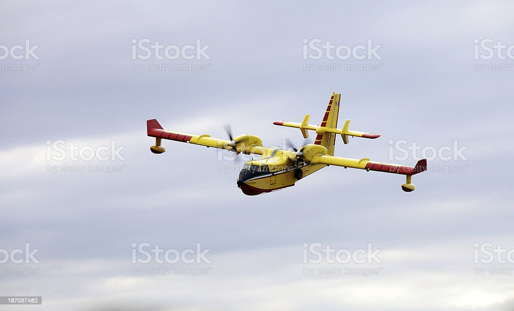 A yellow firefighter airplane flying in a cloudy sky. royalty-free stock photo
