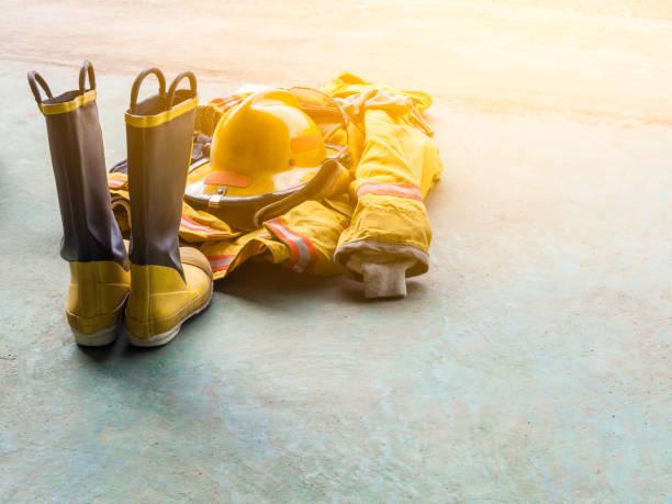 amarillo uniforme ignífugo de los bomberos. en el piso. luz de la llamarada. - bombero fotografías e imágenes de stock