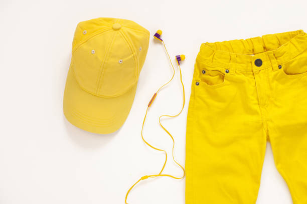yellow flatlay jeans, baseball cap and headphones on white background copy space,top view.spring summer fashion clothing - spring fashion stock pictures, royalty-free photos & images