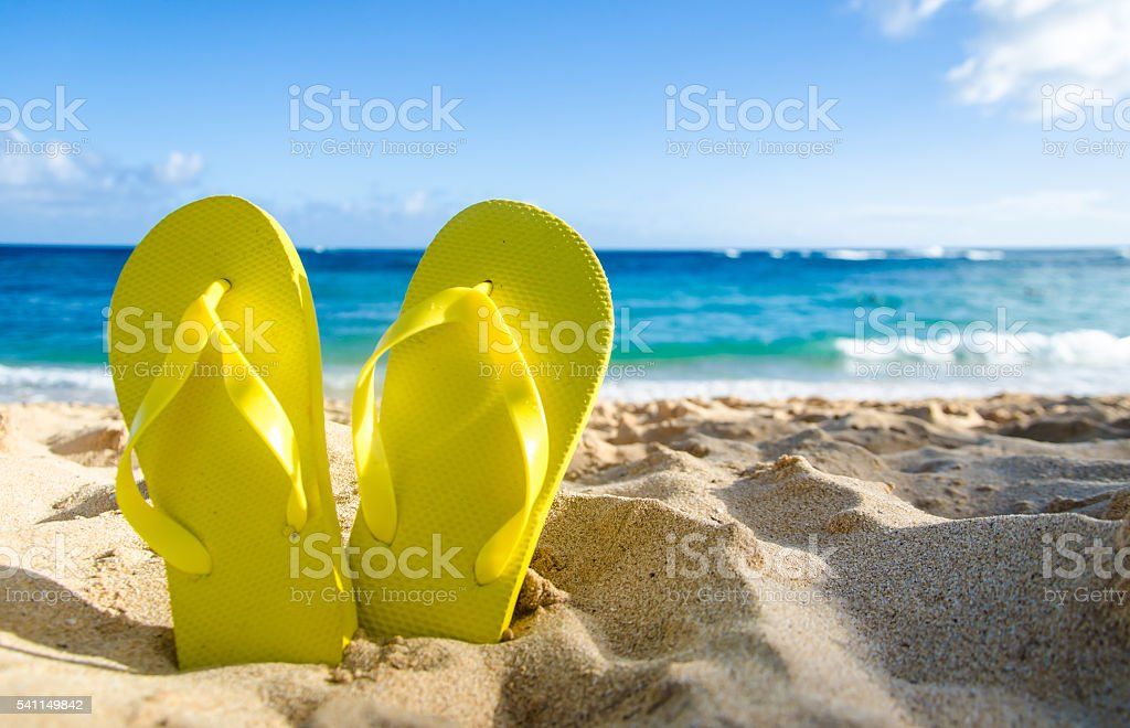 Yellow flip flops on the sandy beach stock photo