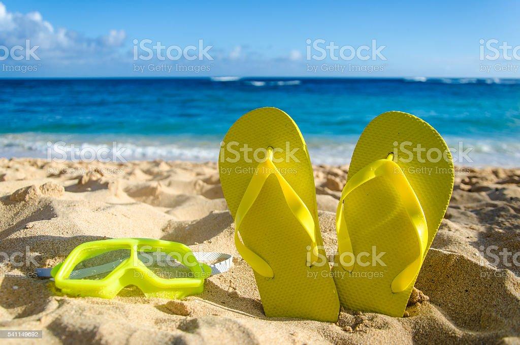 Yellow flip flops with swim glasses on the sandy beach stock photo