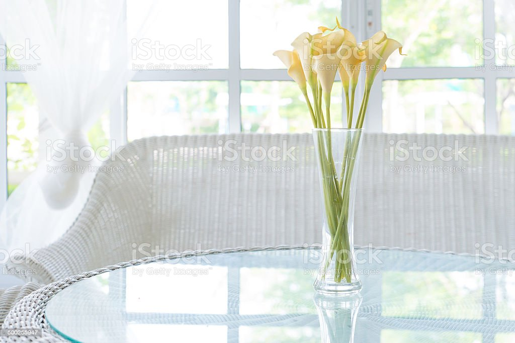 Yellow flower in vase on table and window sill background. stock photo