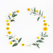 istock Yellow flowers, eucalyptus branches. Flat lay, top view 909730072