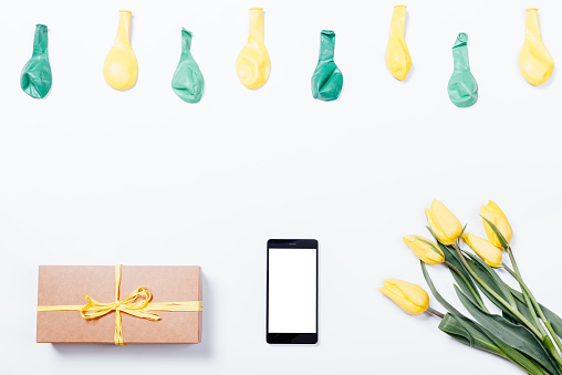 istock Yellow flowers, mobile phone, gift box with a ribbon and balloons on a white table 655818076