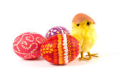 yellow fluffy easter chick sitting behind colorful easter eggs