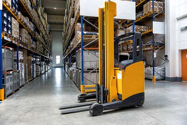 Yellow fork lift stopped in a warehouse Yellow forklift placed inside of new distribution warehouse. pallet jack stock pictures, royalty-free photos & images