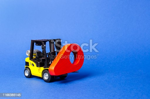 641289780 istock photo Yellow forklift carries a red location pointer. Destination cargo and parcels, tracking. Technological processes at factory. Transportation services and logistics management in production warehouse. 1166385145
