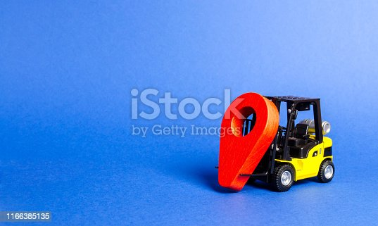 641289780 istock photo Yellow forklift carries a red location pointer. Transportation services and logistics management in production warehouse. Destination cargo and parcels, tracking. Technological processes at factory 1166385135